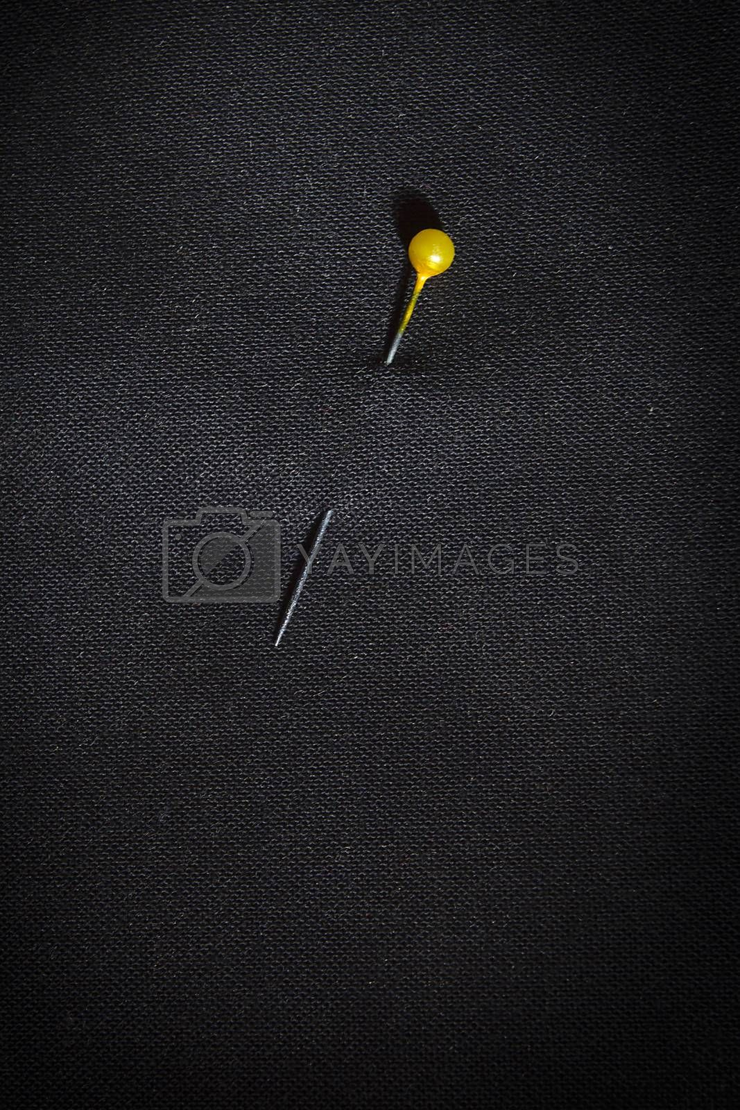 Pin with yellow head in black fabric