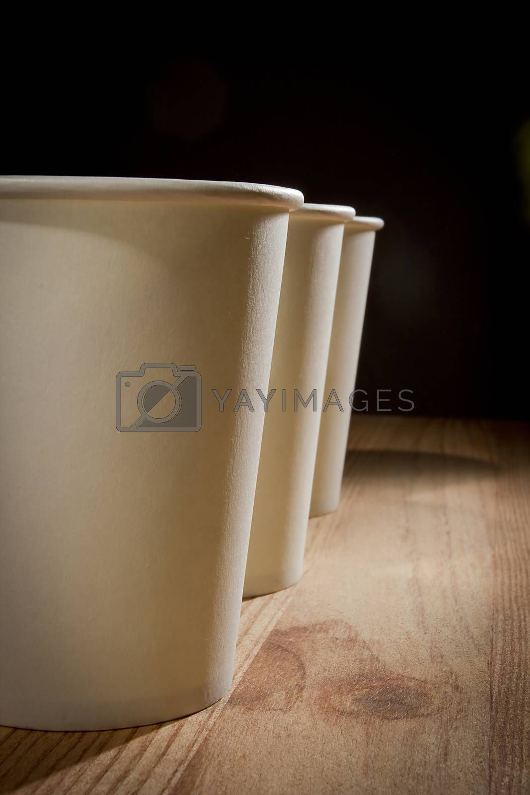 White paper disposable cups on wooden table