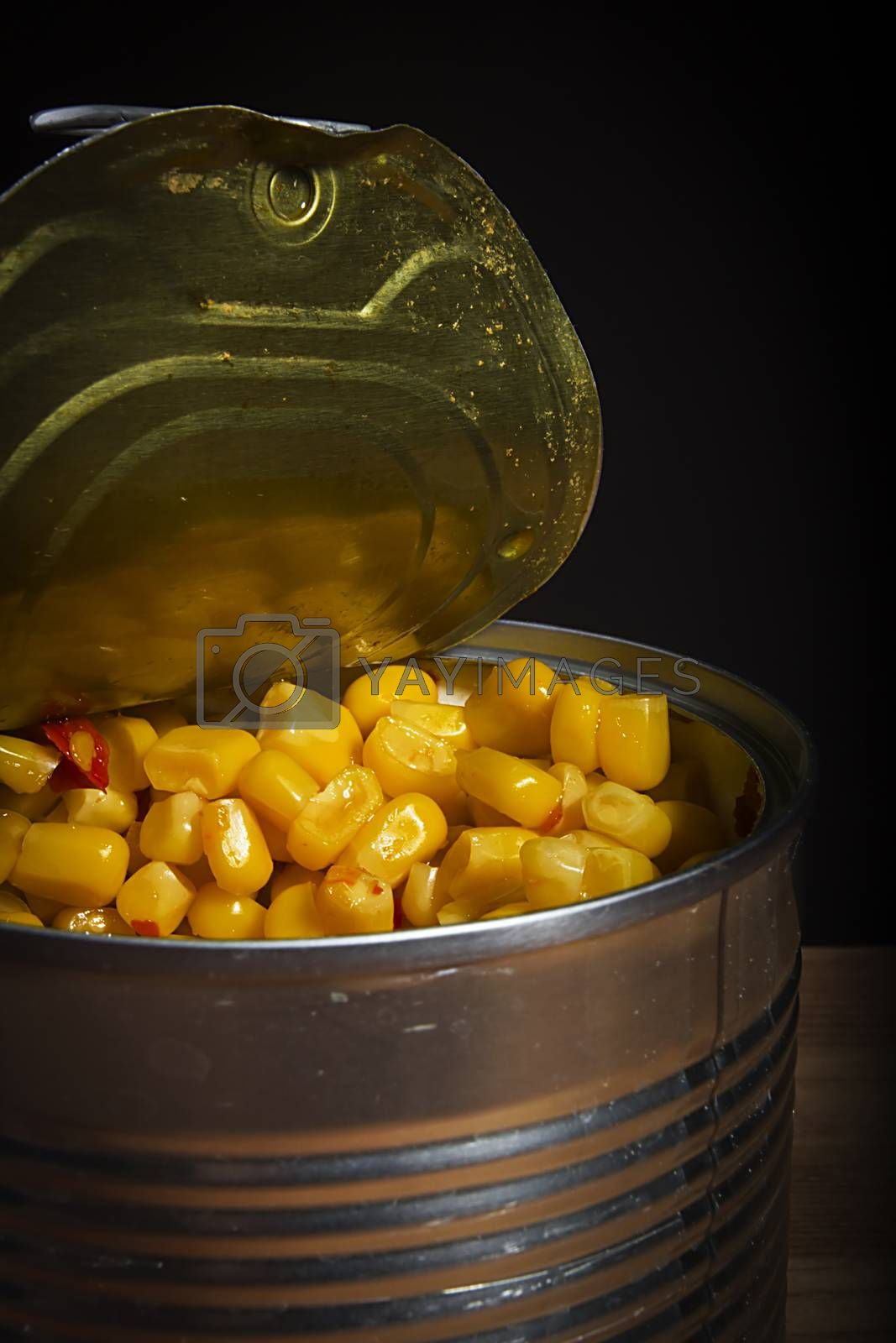 Open tin with canned sweet corn on a black background