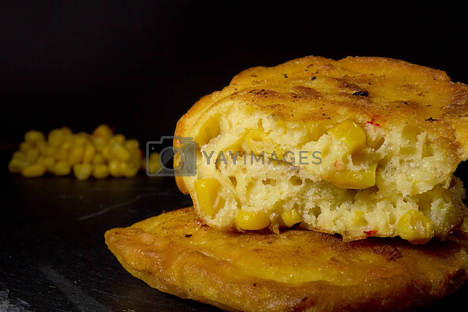 Broken corn pancakes close up on black background