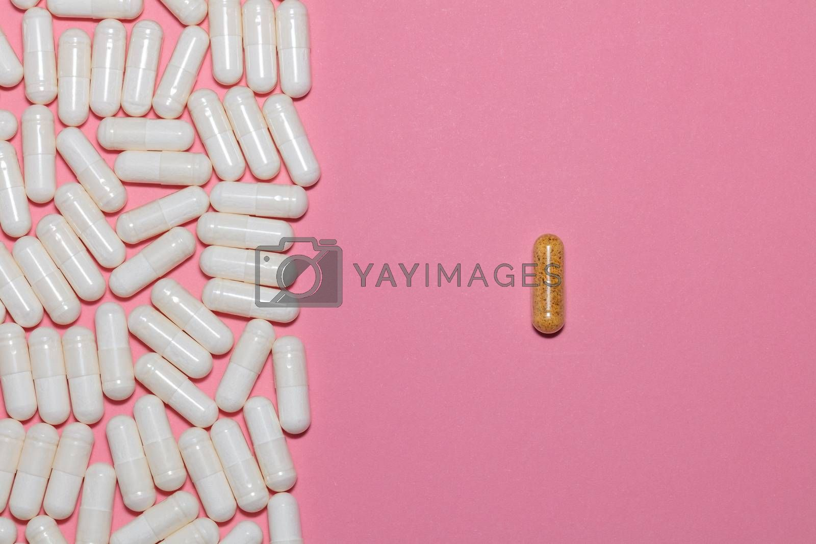Top view of white pills on one side and a single brown pill on the other side on pink background with copy space. Healthcare, medical and pharmaceutical concept.
