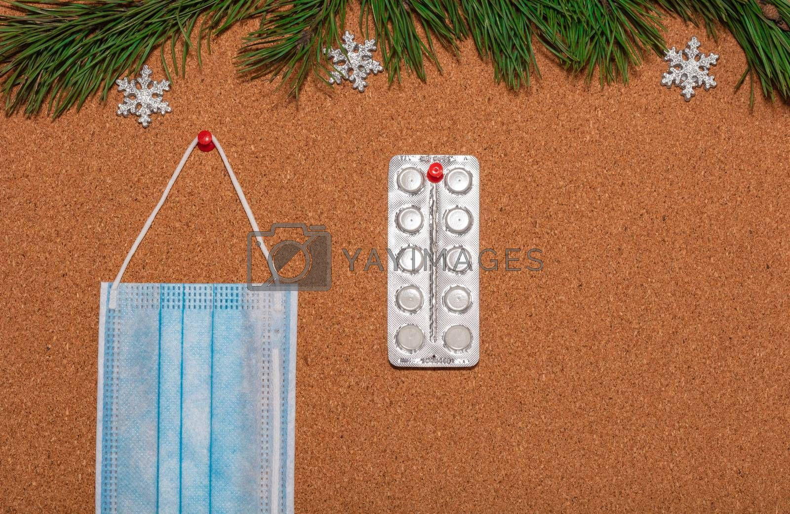Medical mask and white pills pinned on a corkwood notice board which is decorated with pine twigs and silver snowflakes at the top. Healthcare, christmas, new years celebration, new normal concepts.