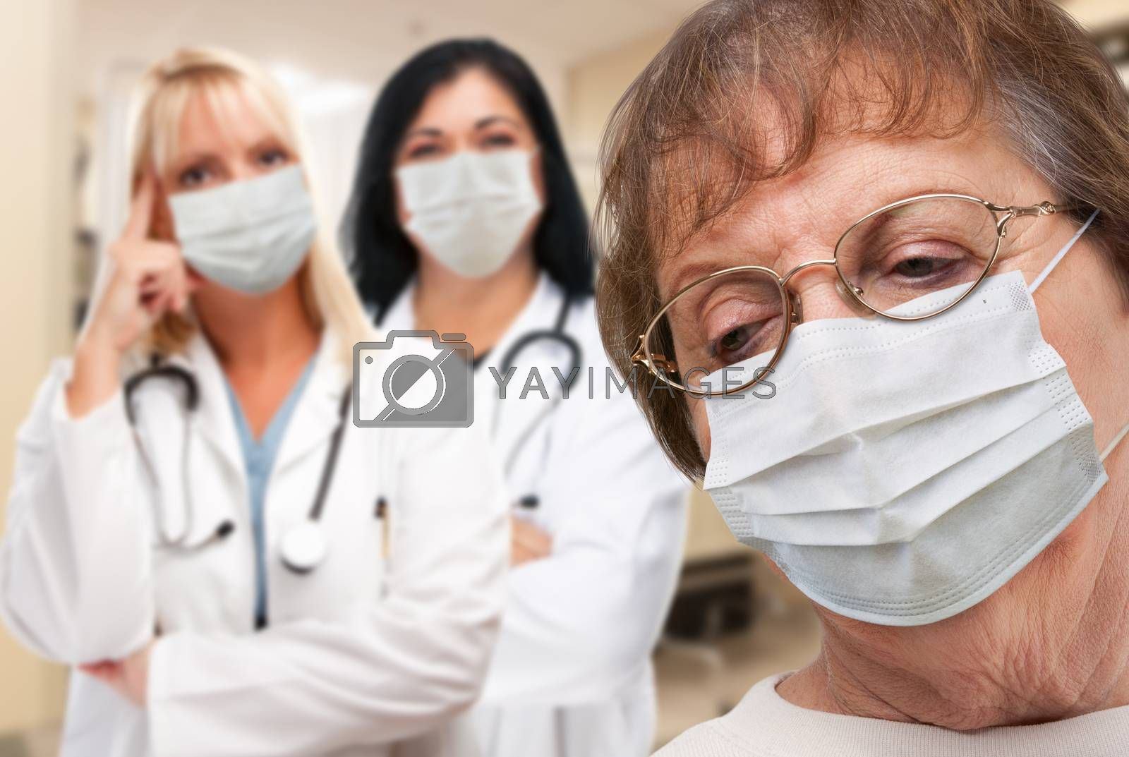 Senior Adult Female Looking Down as Doctors stand Behind All Wearing Medical Face Masks.