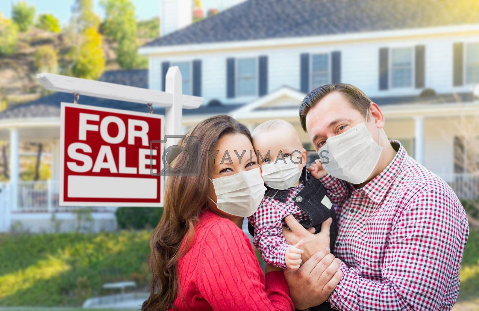 Happy Young Family Wearing Medical Face Masks In Front of New House and Sold For Sale Sign.
