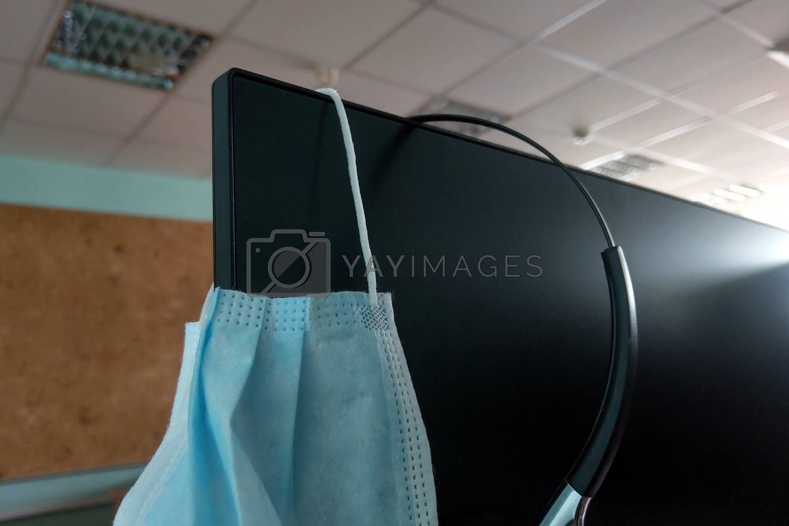 A medical mask hangs on the computer monitor. COVID protection - 19