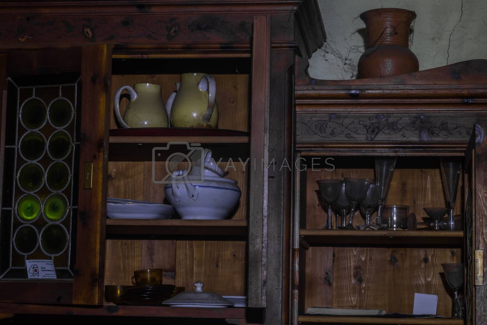 pots glasses in a wooden shelf in a house from a hunter