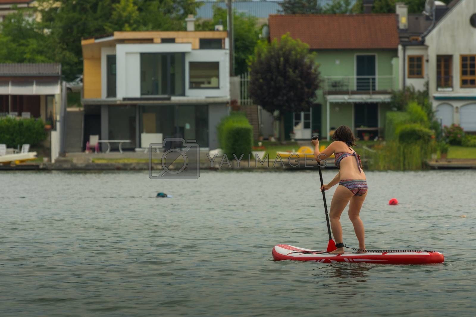 woman with stand up paddle by the lake in summer