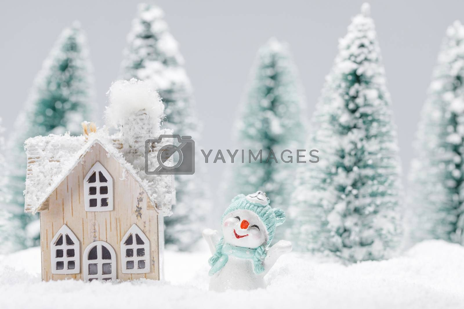 Small decorative snowman with gift near wooden house in fir forest under falling snow