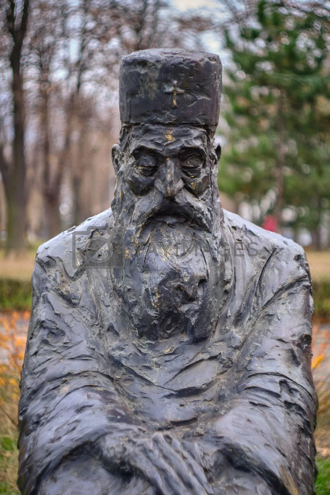 Belgrade / Serbia - December 21, 2019: Statue of Serbian Patriarch Pavle, the 44th Patriarch of the Serbian Orthodox Church, in Tasmajdan park near St. Mark's Church in Belgrade, Serbia