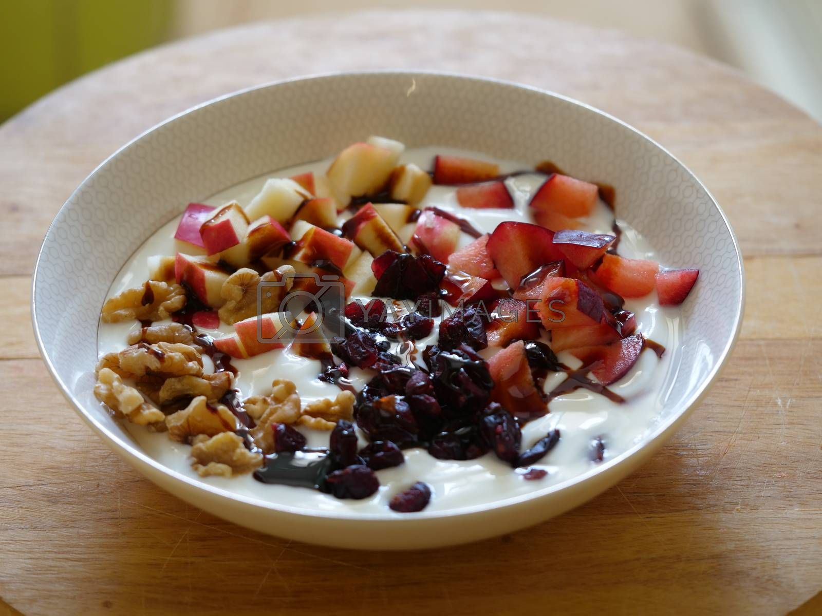 Bowl of yogurt with fresh fruits cubes nuts and silan