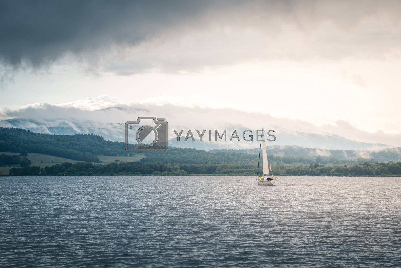 Royalty free image of Sailing boat floats on the lake with stormy clouds sky. Autumn sailboat ship water sport scene from Lipno, Czech republic, Sumava. by petrsvoboda91