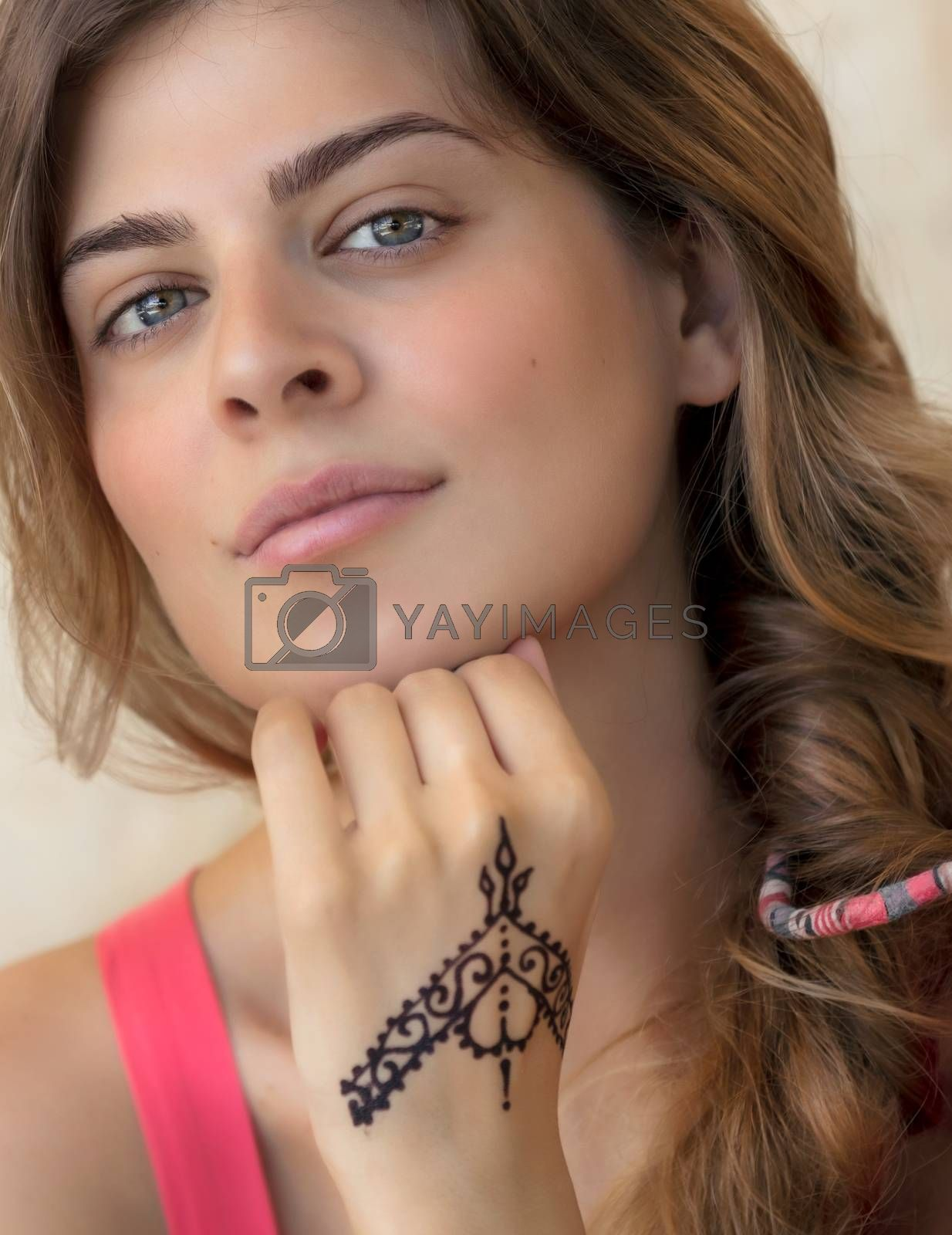 Closeup Genuine Portrait of an Attractive Woman Isolated on Beige Background with Beautiful Tattoo on the Hand. Stylish Body Art. Natural Beauty of Young Female.