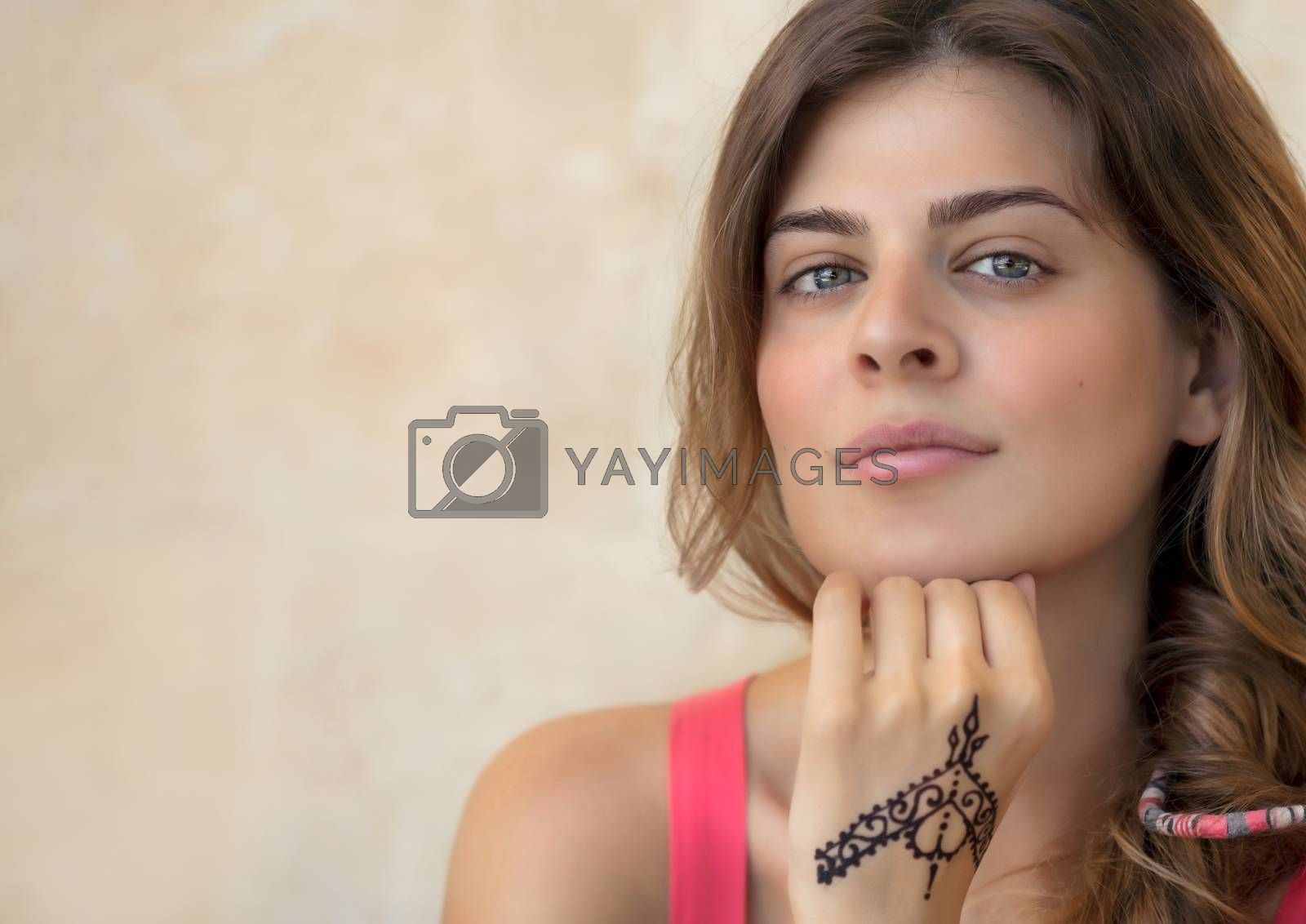 Portrait of an Attractive Woman Isolated on Beige Background with Beautiful Mehndi Drawing on the Hand. Stylish Body Art. Natural Beauty of Young Female. Photo with Copy Space.
