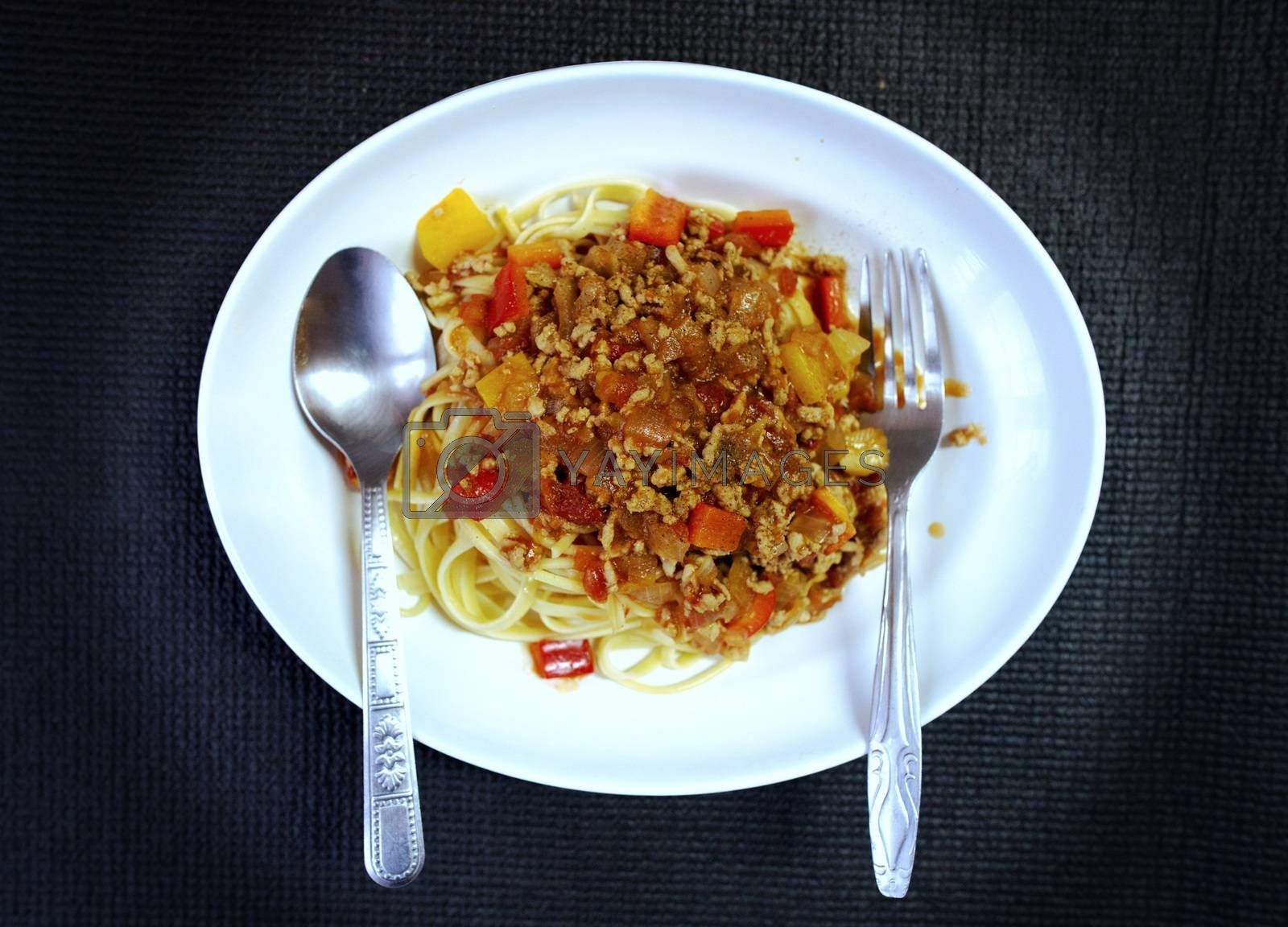 Vintage image of pork chop spaghetti, applied Thai style, top from white, isolated on black background.
