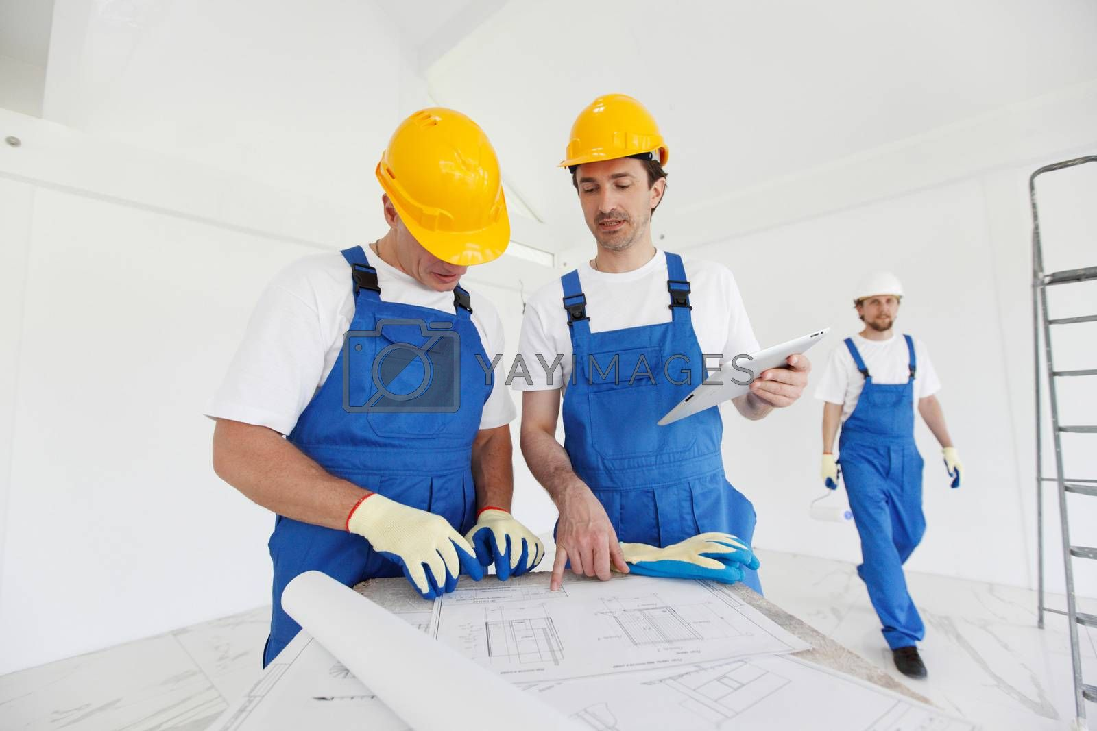 Workers in blue uniform and yellow hardhats with blueprint working at construction site