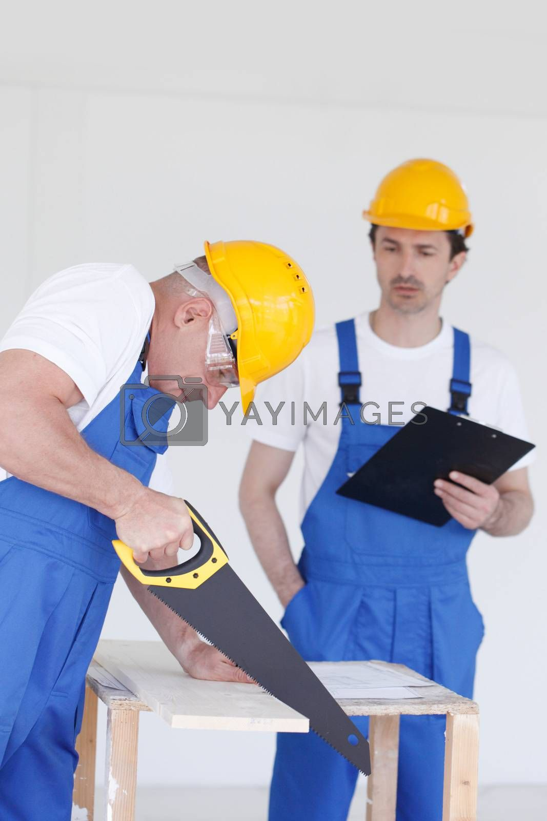 Business, building, teamwork and people concept - group of builders in hardhats with tools indoors