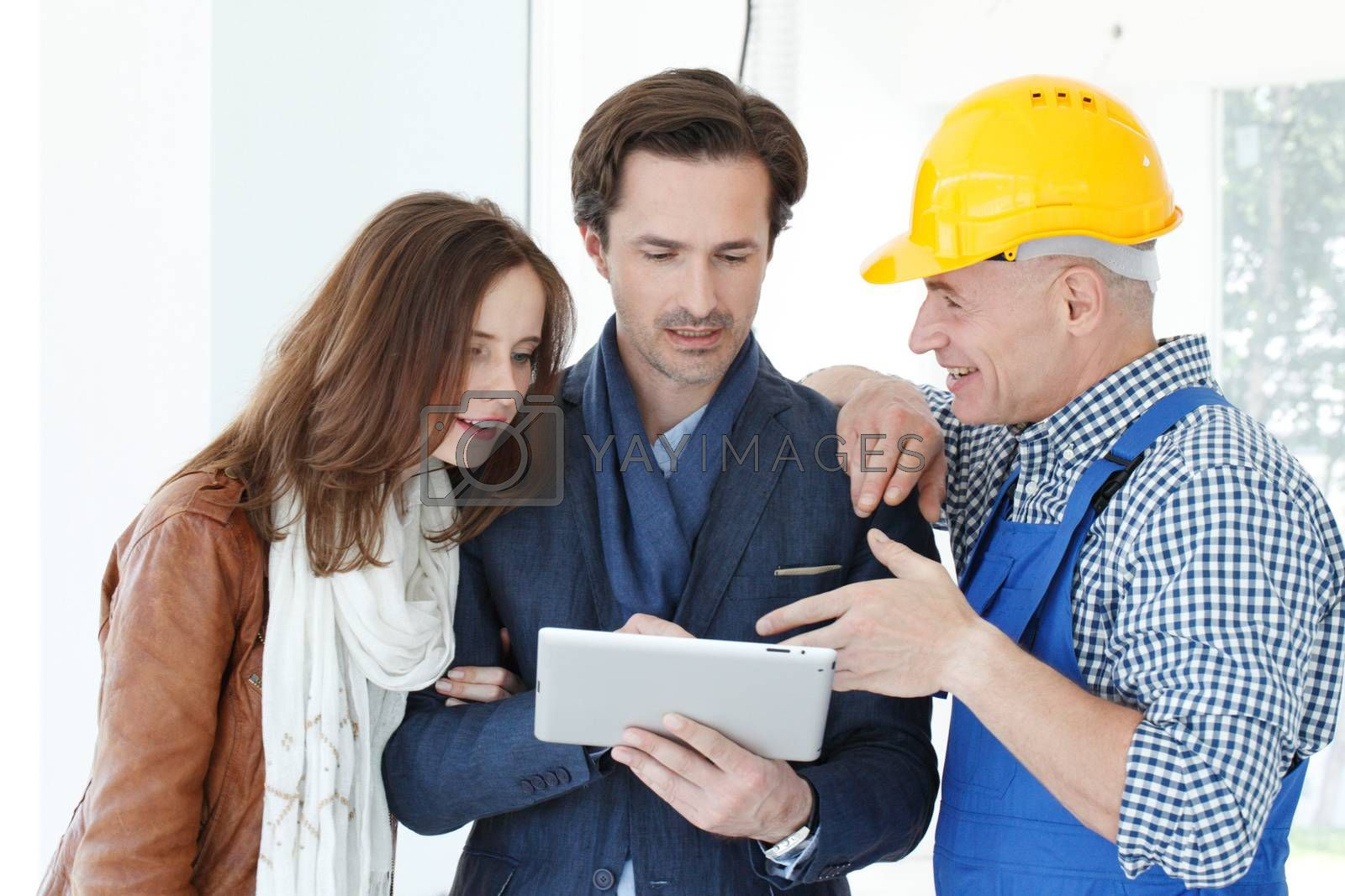 Worker and couple using tablet pc at construction site planning renovation house design plans