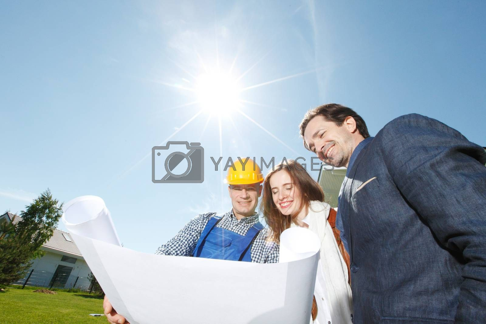 Foreman showing holding house design construction plan to a happy young couple new house real estate concept