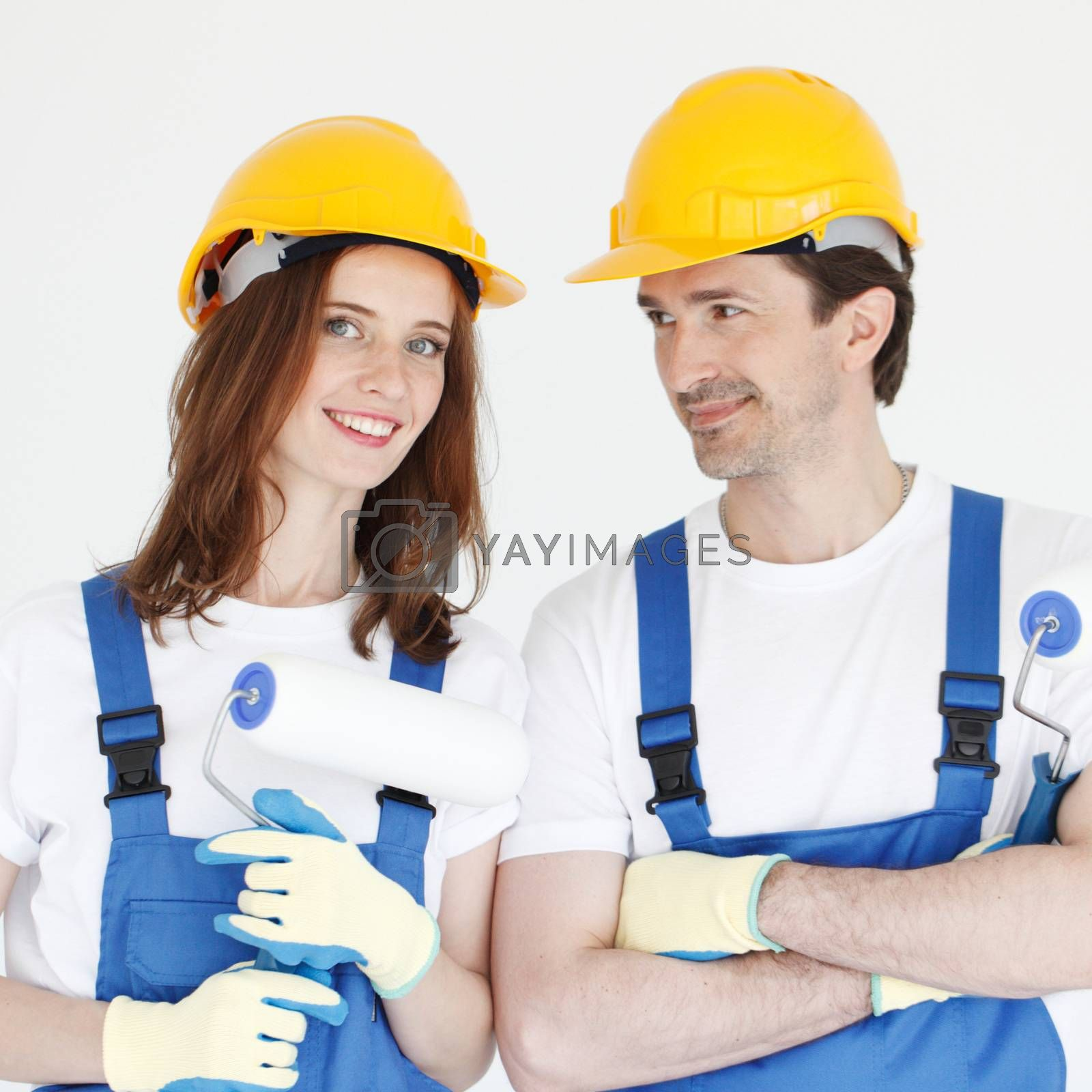 Two young workers in uniform of coverall and hardhat with paint rollers