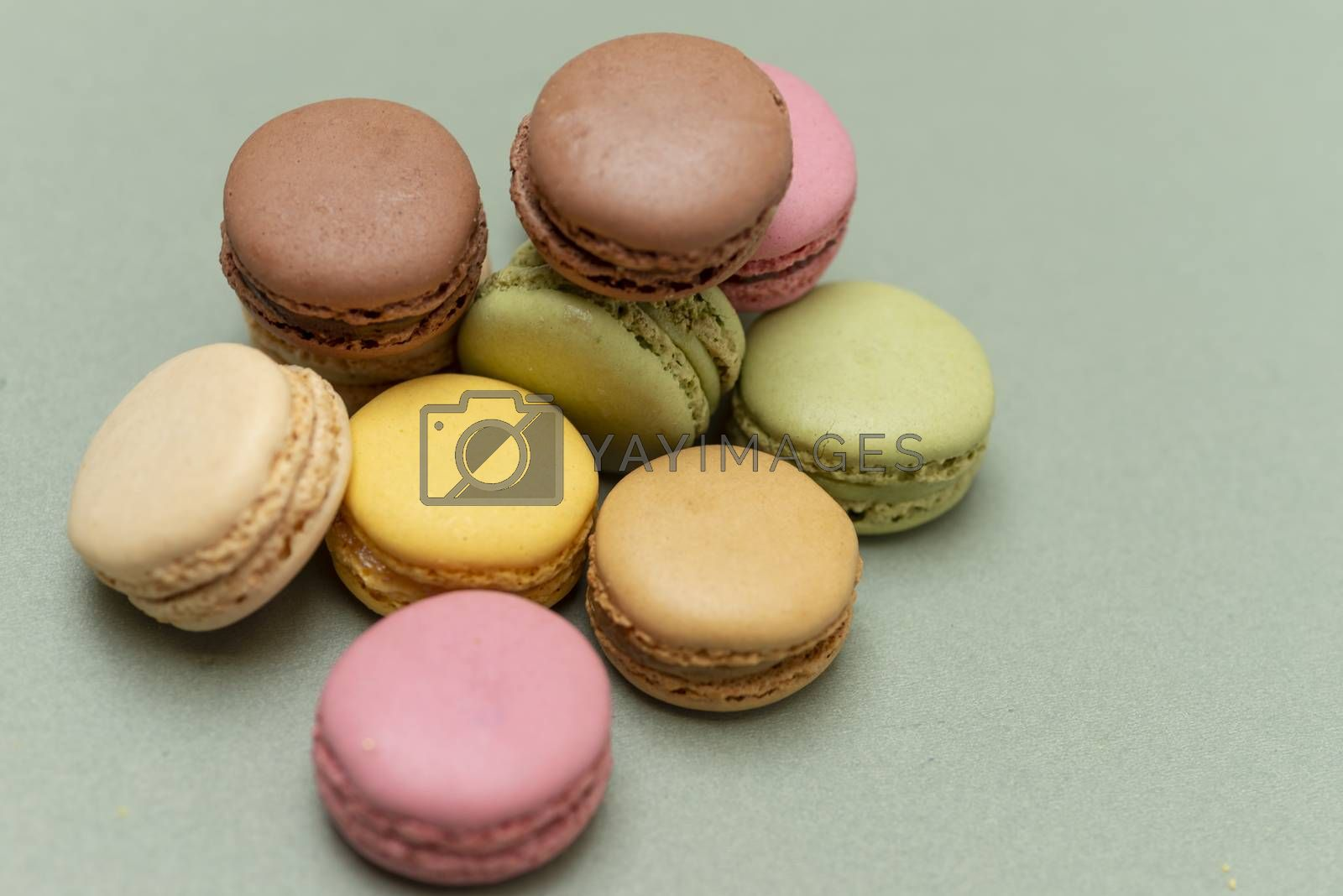 Assorted colored tasty macaroons over a green background.