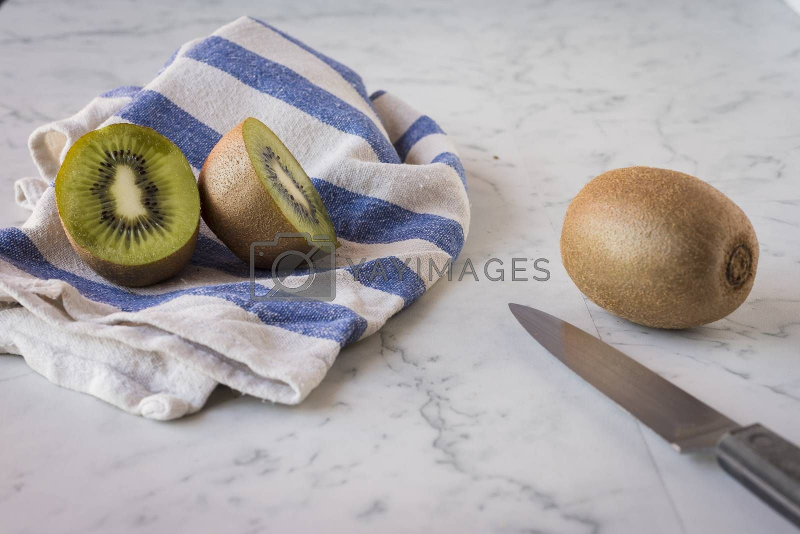 Two green and fresh kiwis on marble surface
