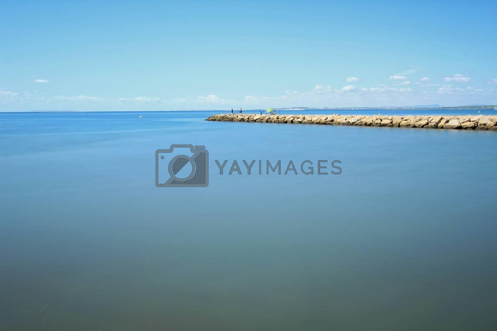 Fishing day on a breakwater under the sun in Santa Pola, Spain