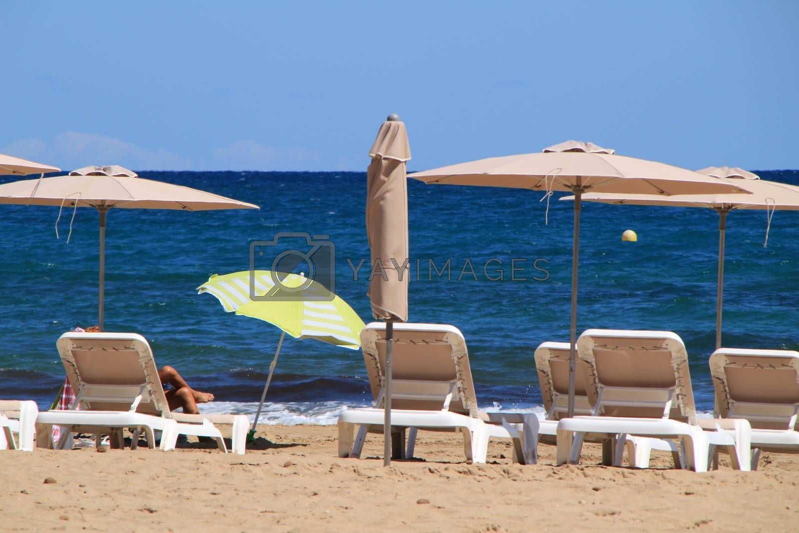 Woman sunbathing on a beach in Alicante and surrounded by sunbeds and umbrellas