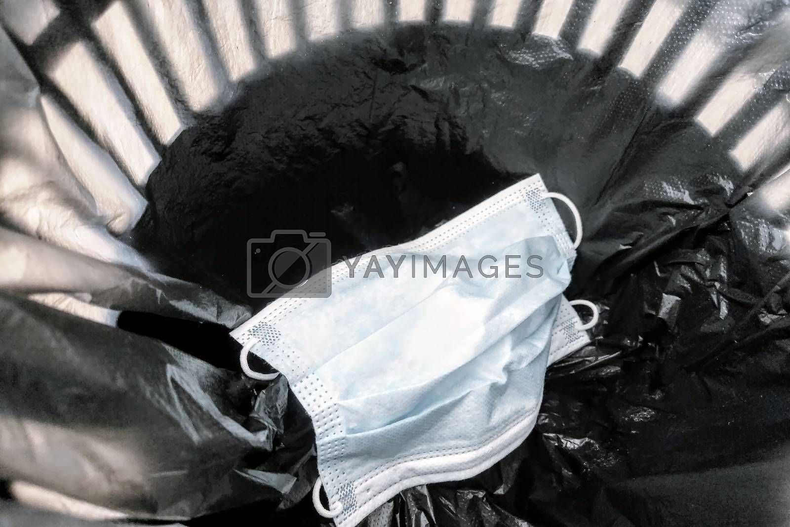 Used medical mask in the rubbish bin. Coronavirus protection