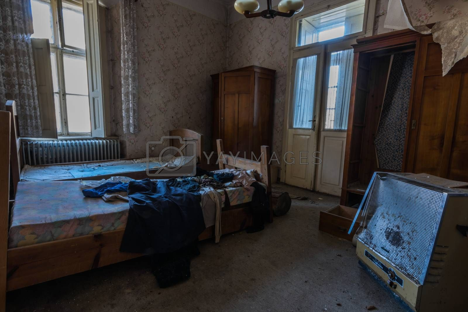 abandoned hotel room with beds and heating