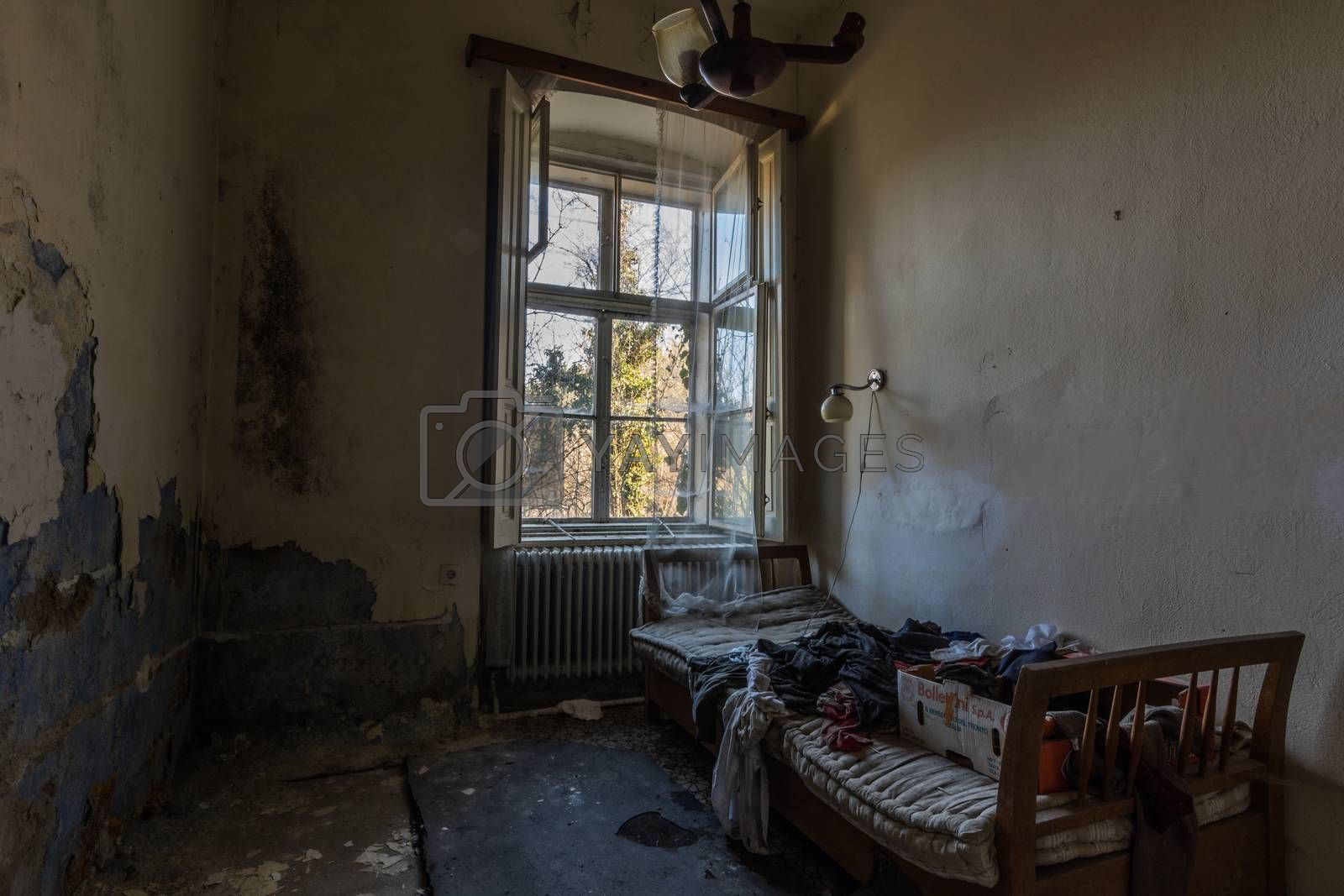 abandoned hotel room with bed and open window in the mountains
