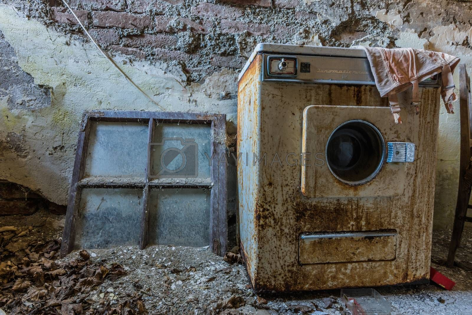 rusty old washing machine in an abandoned hotel