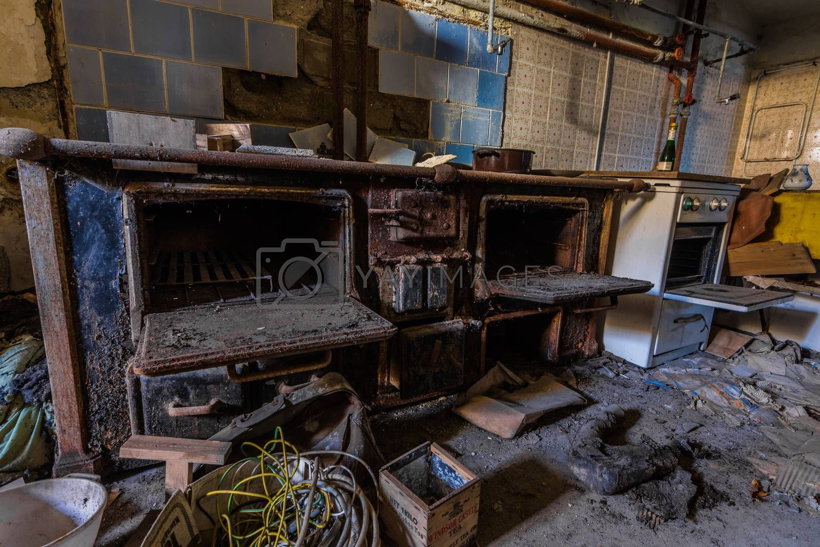 large rusty oven in an abandoned hotel kitchen
