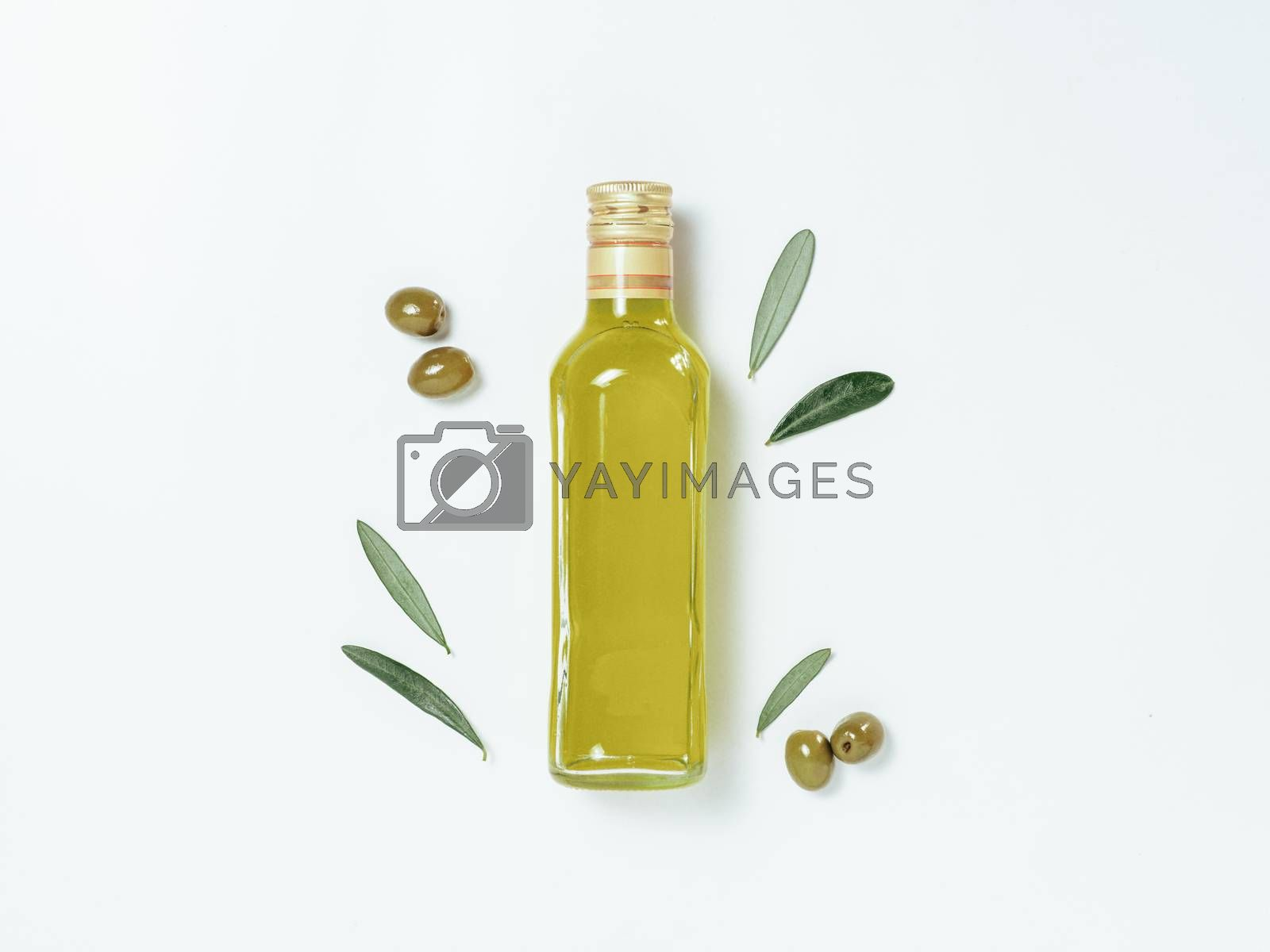 Olive oil glass bottle mock up. Top view of clear glass bottle with olive oil on white background with green olives and fresh green olive tree leaves. Copy space.