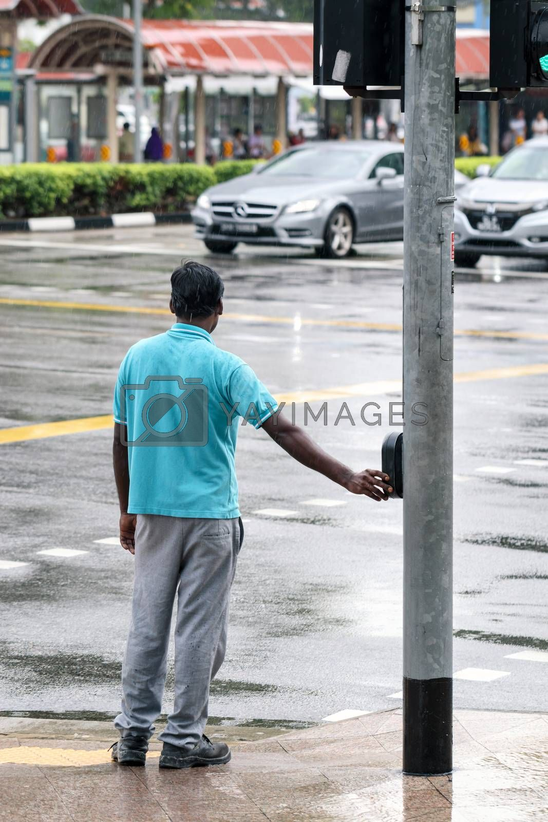 pedestrian pushing button on traffic light pole to get green sign for safely crossing street at intersection, people crossing the street, waiting for flashing lights of walk or don't walk