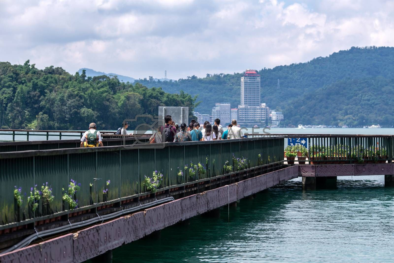 Tourists walk on pier for Hop-On Hop-Off Boat at Sun Moon Lake, the largest lake in Taiwan and tourist attraction. There are 3 main piers at Sun Moon Lake.