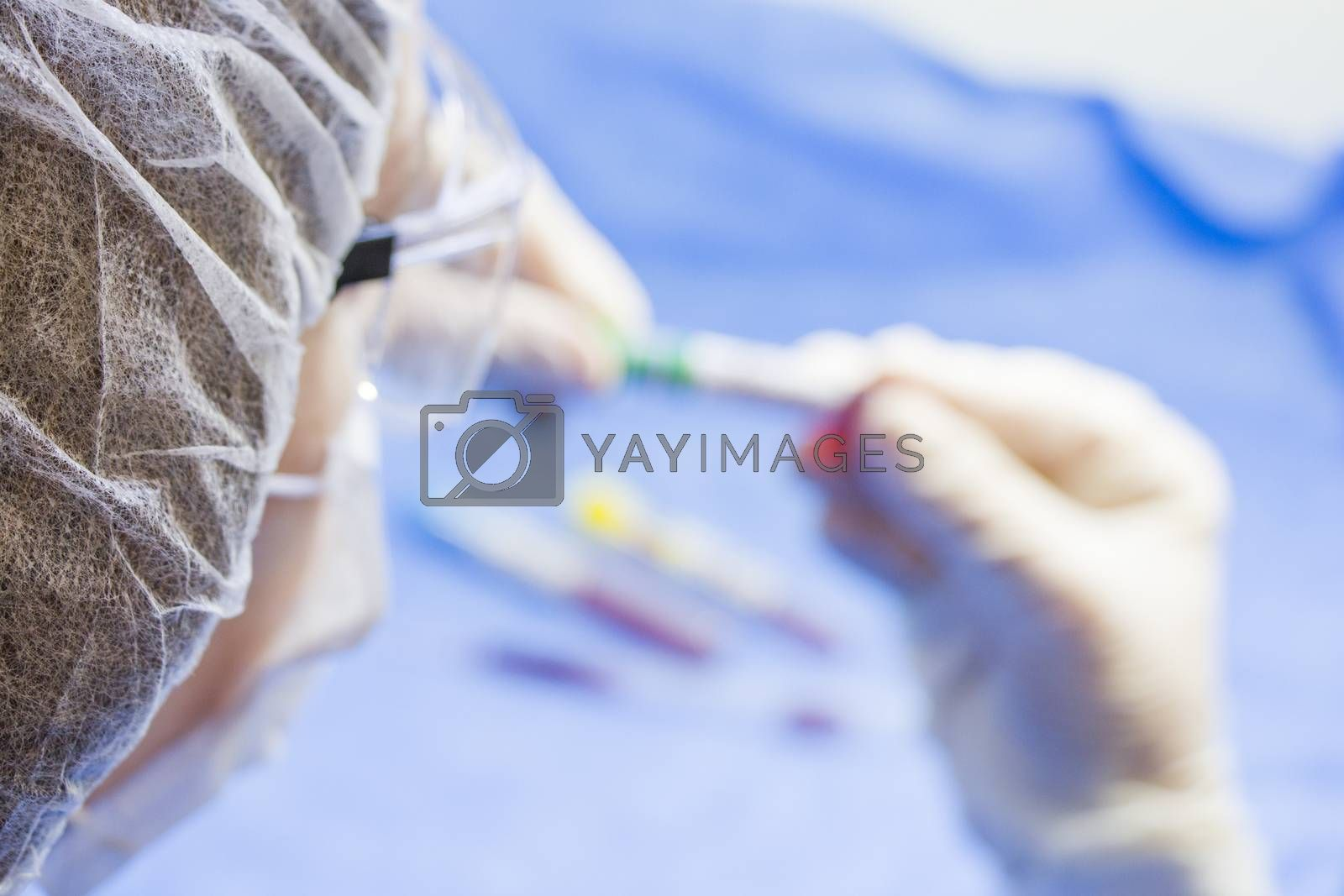 Doctors face and hands, tube and glove, laboratory situation. Blur photo for copy space.