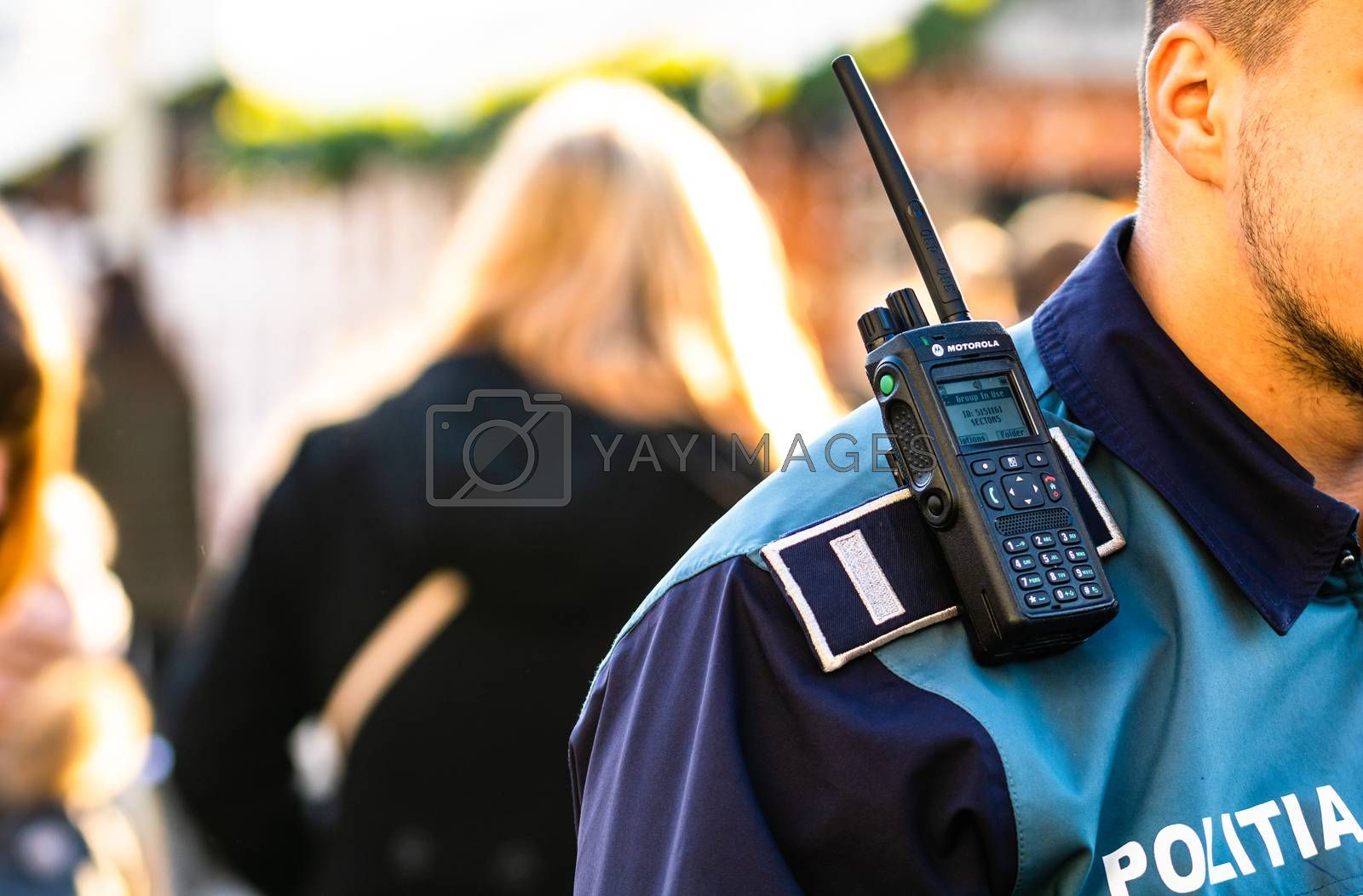 Police officer holding walkie talkie on his shoulder during intervention in Bucharest, Romania, 2020