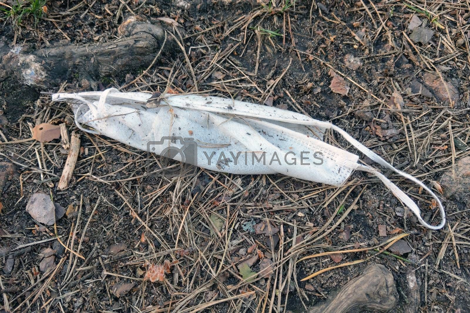 The used medical mask lies on the ground. Environmental pollution. Coronavirus protection