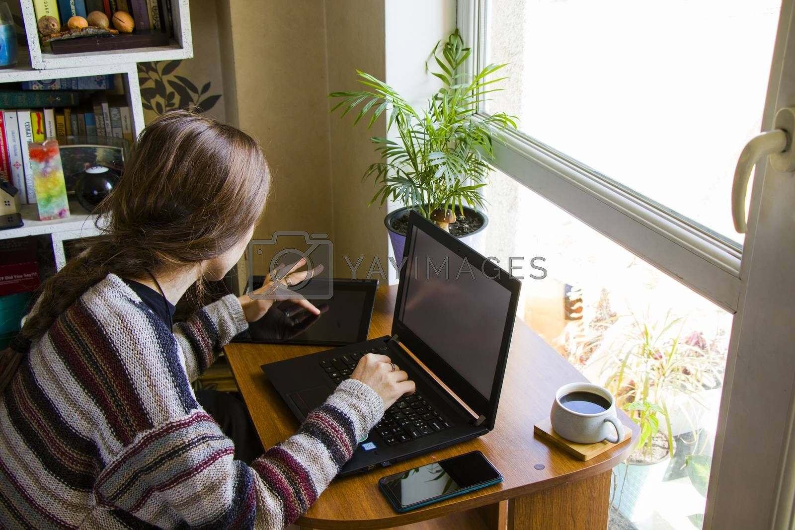 Tbilisi, Georgia - October 09, 2020: Woman working with notebook in workplace, digital tablet, mobile phone, coffee and plants in workspace, home working