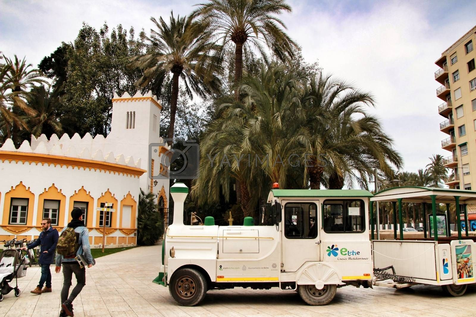 Elche, Alicante, Spain- February 19, 2019: Guided tour on Tourist train through the streets and palm groves in winter under blue sky. Tourist Office in the background.