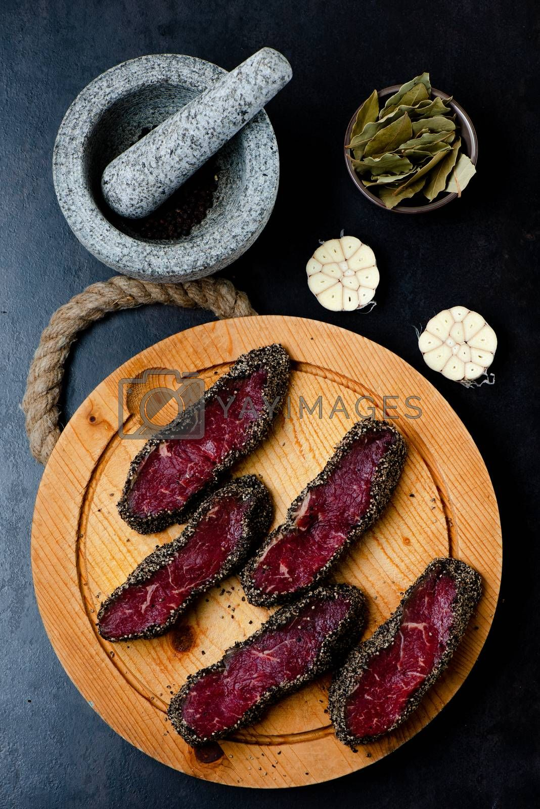 Stone mortar bowl with pestle, garlic, bay leaf and wooden cutting board with raw pepper steaks on stone surface