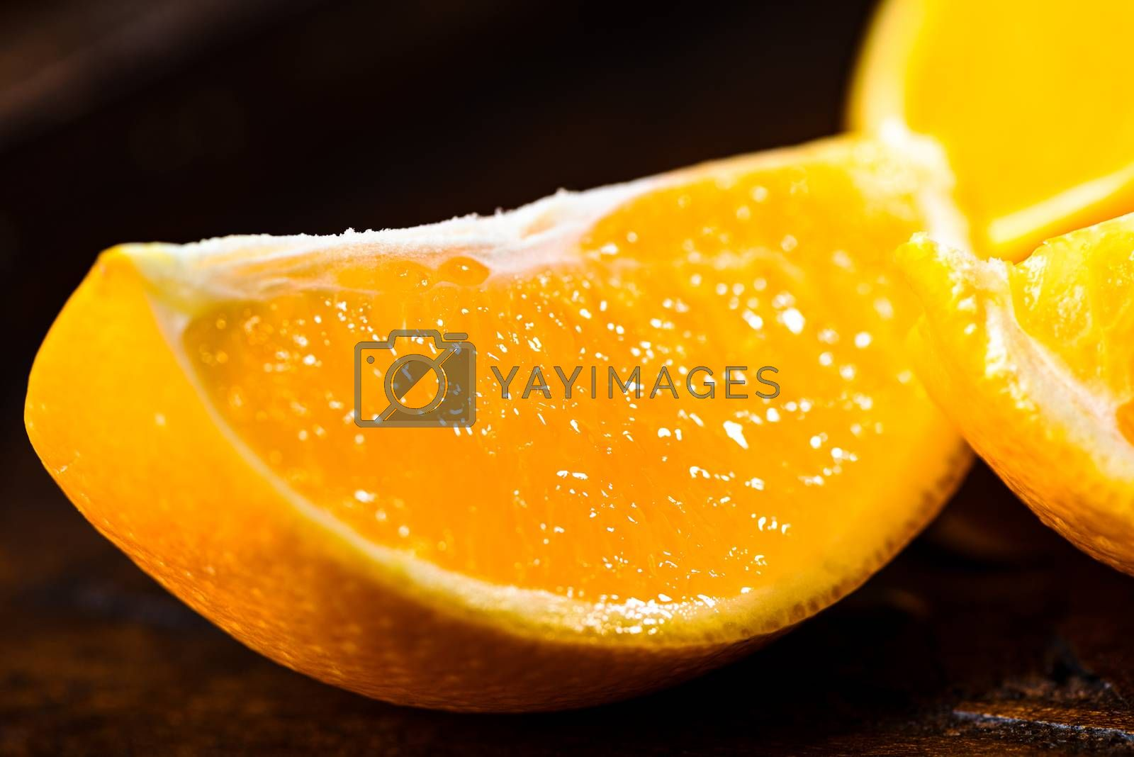 Sliced close up oranges on dark background with selective focus