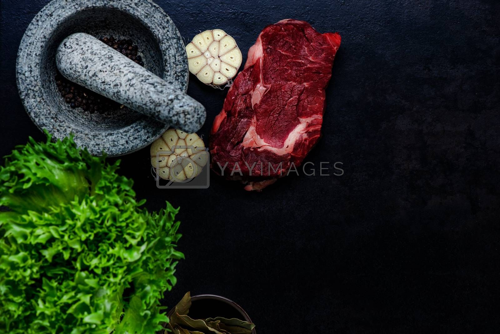 Stone mortar bowl and pestle with raw steak, garlic, bay and salad leaves