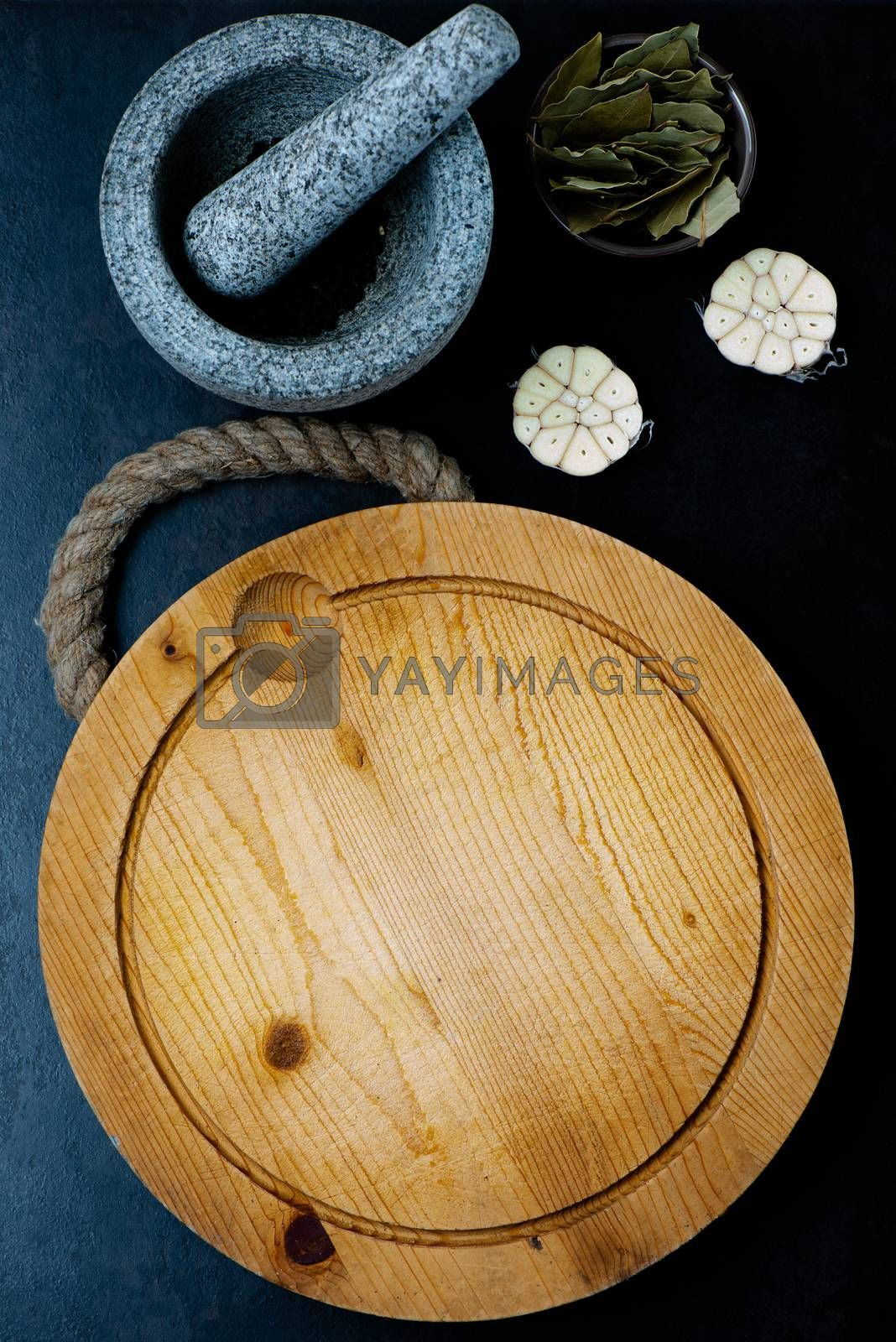Stone mortar bowl with pestle, garlic, bay leaf and wooden cutting board on stone surface
