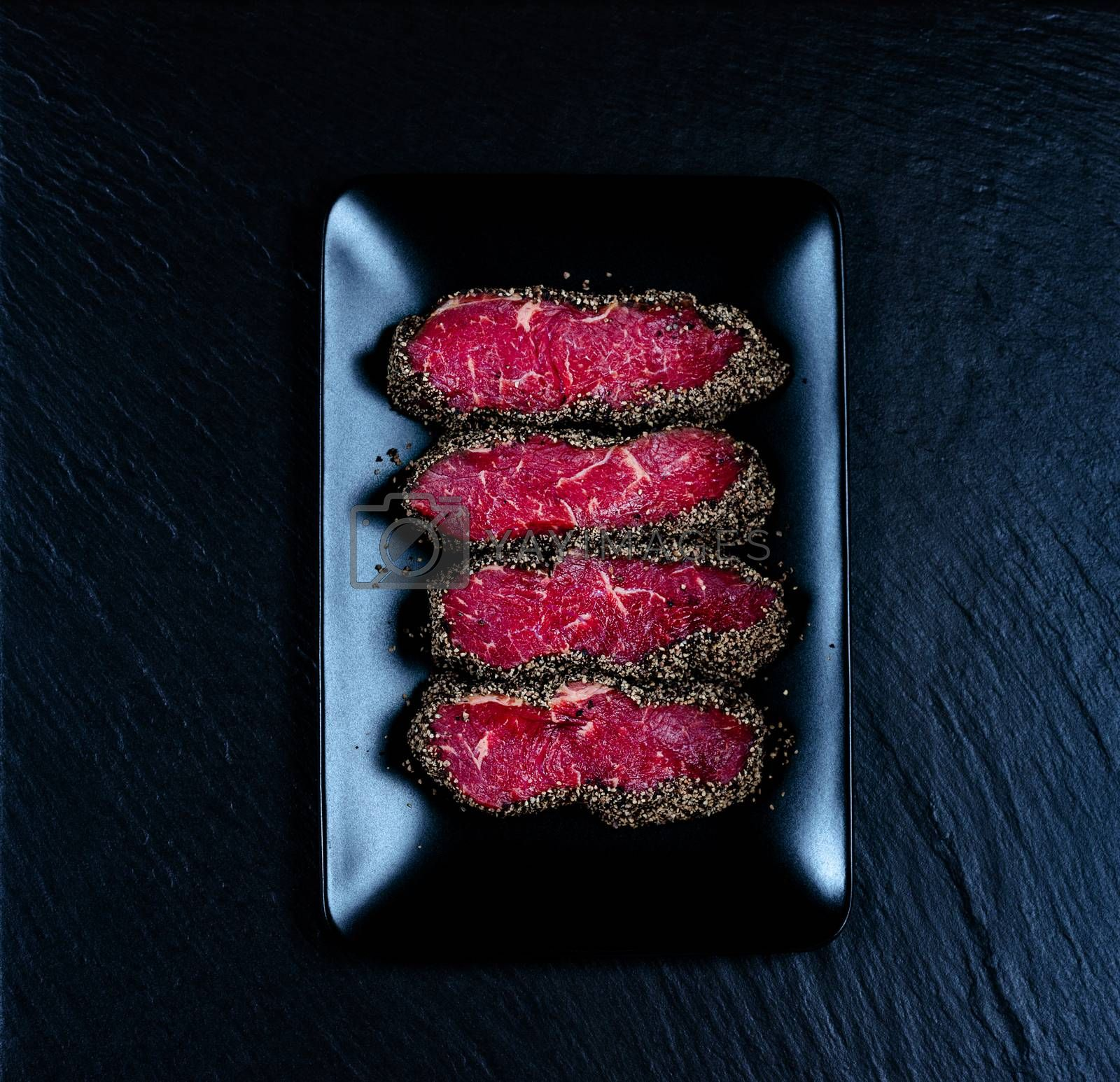 Pepper steaks on black stone plate top view