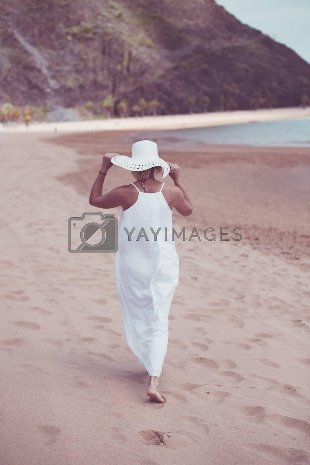 Model in white dress and hat enjoying walk on sandy beach