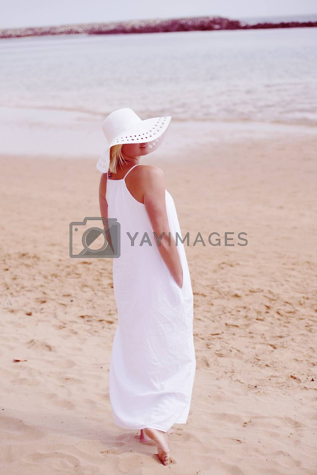 Woman walking on beach in long white dress and hat