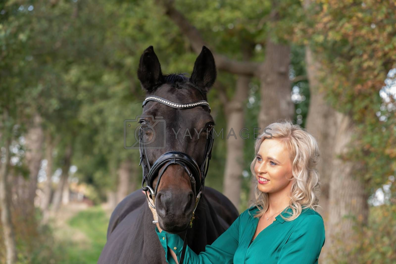 Happy beautiful blond girl in a green dress, cuddling her horse outdoors. Selective focus on the horse, autumn colos. Narrow depth of field, copy-space.