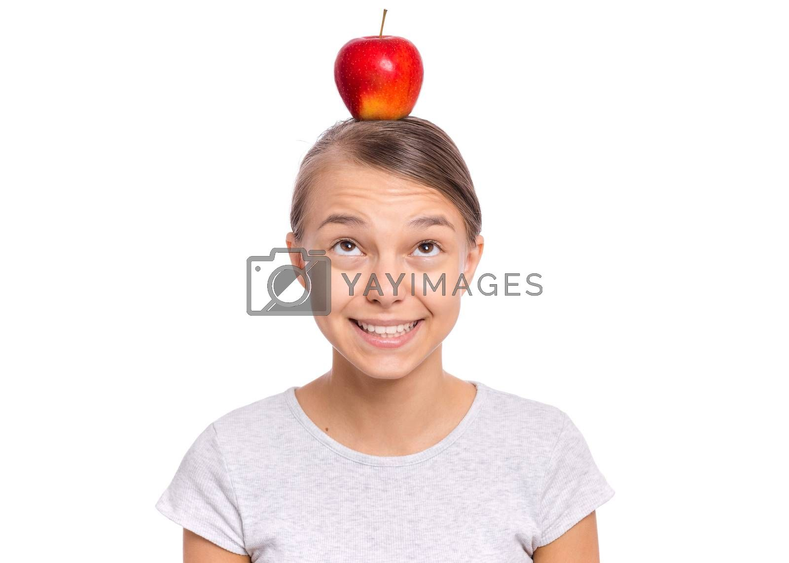 Happy beautiful young teen girl with apple on head, isolated on white background