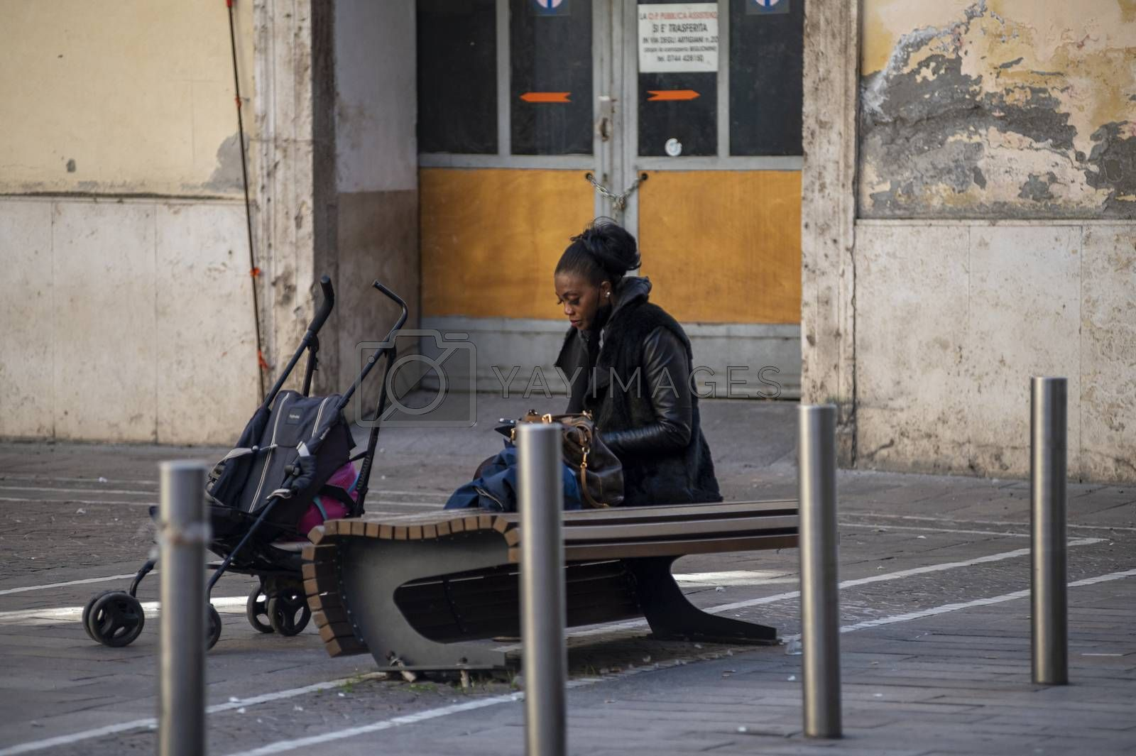 terni,italy october 21 2020:black woman sitting on a bench with a small stroller